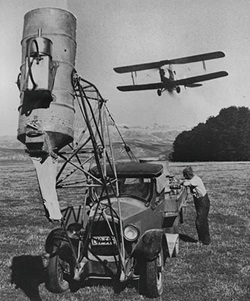 This is how Spreading Fertiliser by air started early in the 1950's, it came to be known as Aerial Topdressing. The Tiger Moth flying above the home made loader is similar to the one John crashed on his first day in business.